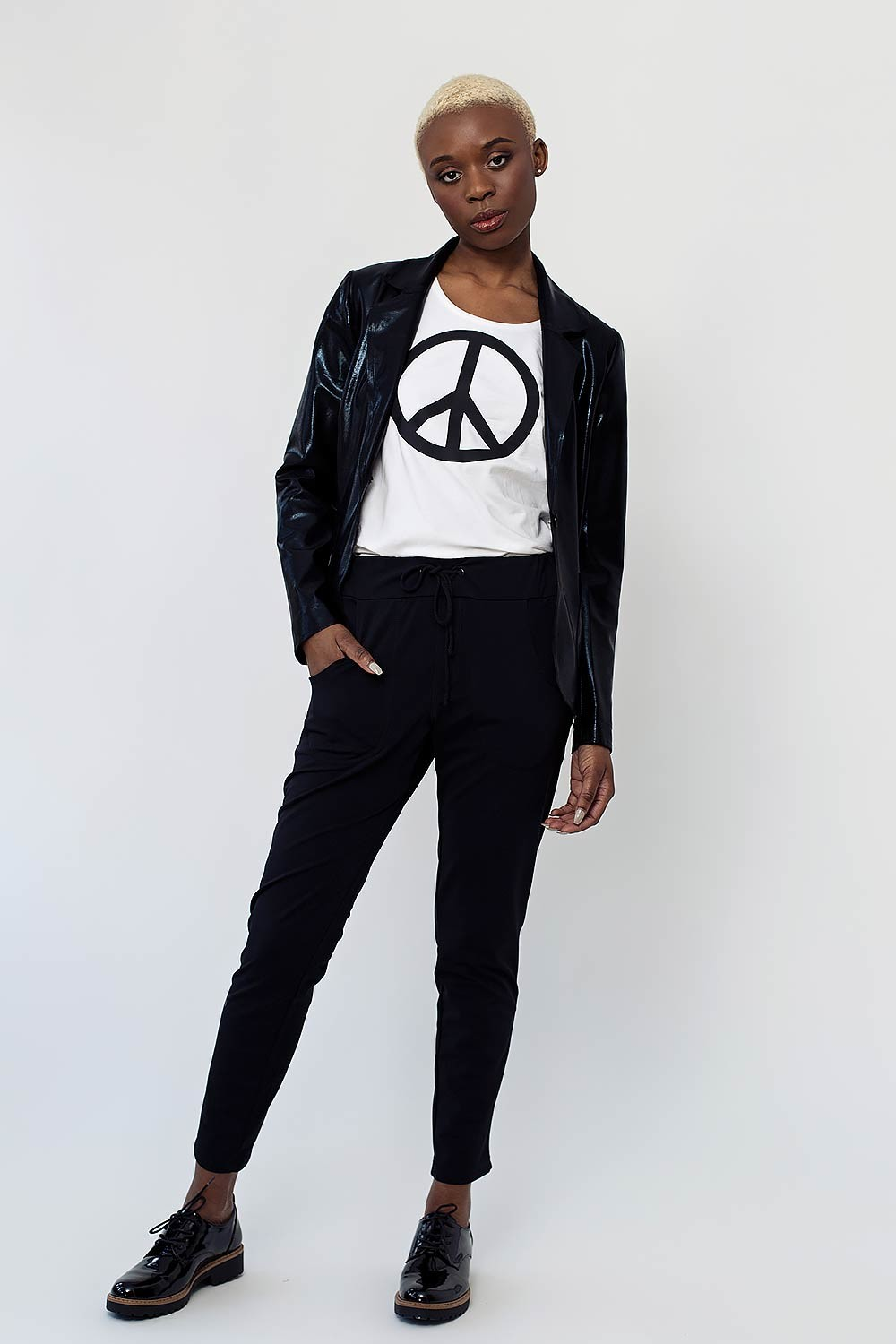 white t-shirt with peace sign, black sweatpants and stretch shiny jacket