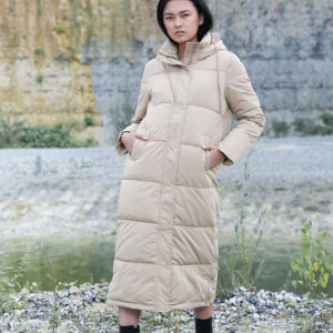 model in sand color long padded coat with hood